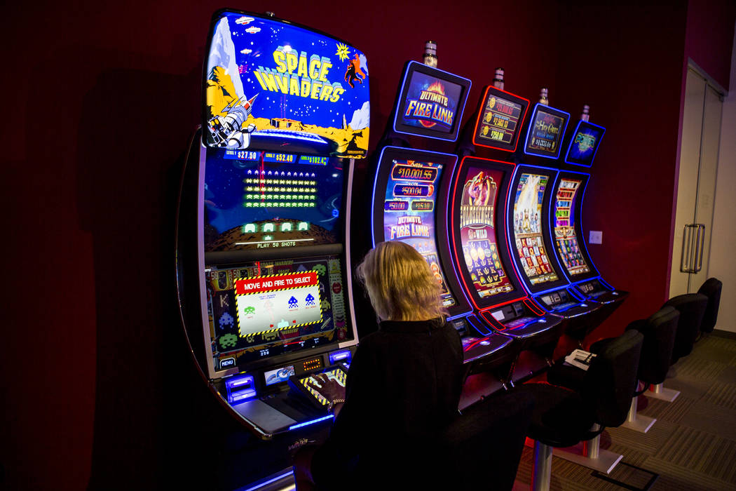 Susan Cartwright, vice president of corporate communications at Scientific Games, demonstrates the new Space Invaders slot machine at the company's office on Thursday, June 8, 2017.  Patrick Conno ...