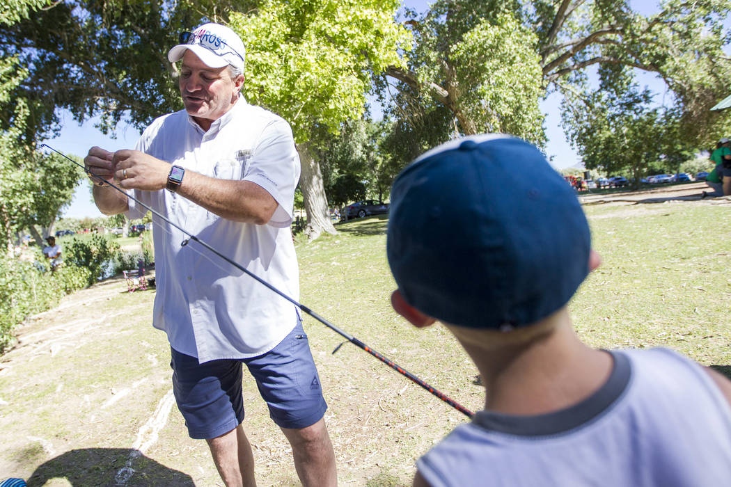 Las Vegas Councilman Steve Ross helps eight-year-old Gavin Phillips with his lure choice during a fishing derby held by the Las Vegas City Council at Floyd Lamb Park at Tule Springs in northwest L ...