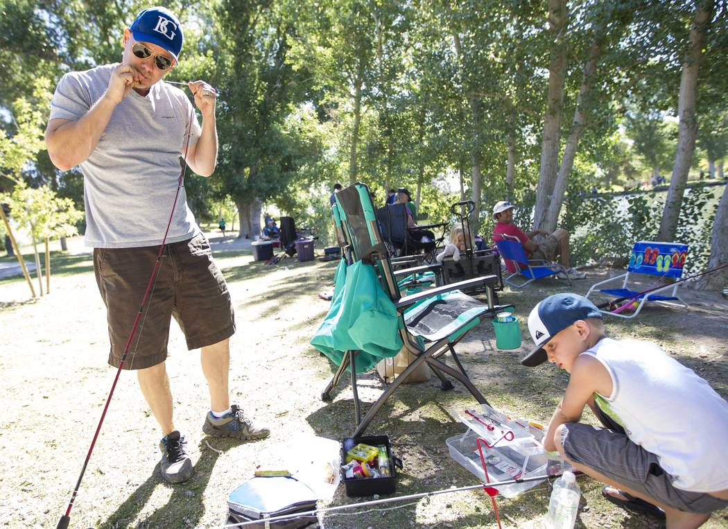 Las Vegas residents Jason Parochniak and eight-year-old prepare their fishing poles during a fishing derby held by the Las Vegas City Council at Floyd Lamb Park at Tule Springs in northwest Las Ve ...