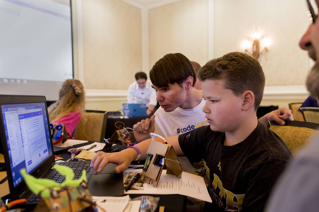 Code Central instructor Sam Cornelius, left, and Sam Chalfant, 12, code during an  interactive seminar on cyber security hosted by the Colloquium for Information Systems Security Education (CISSE) ...
