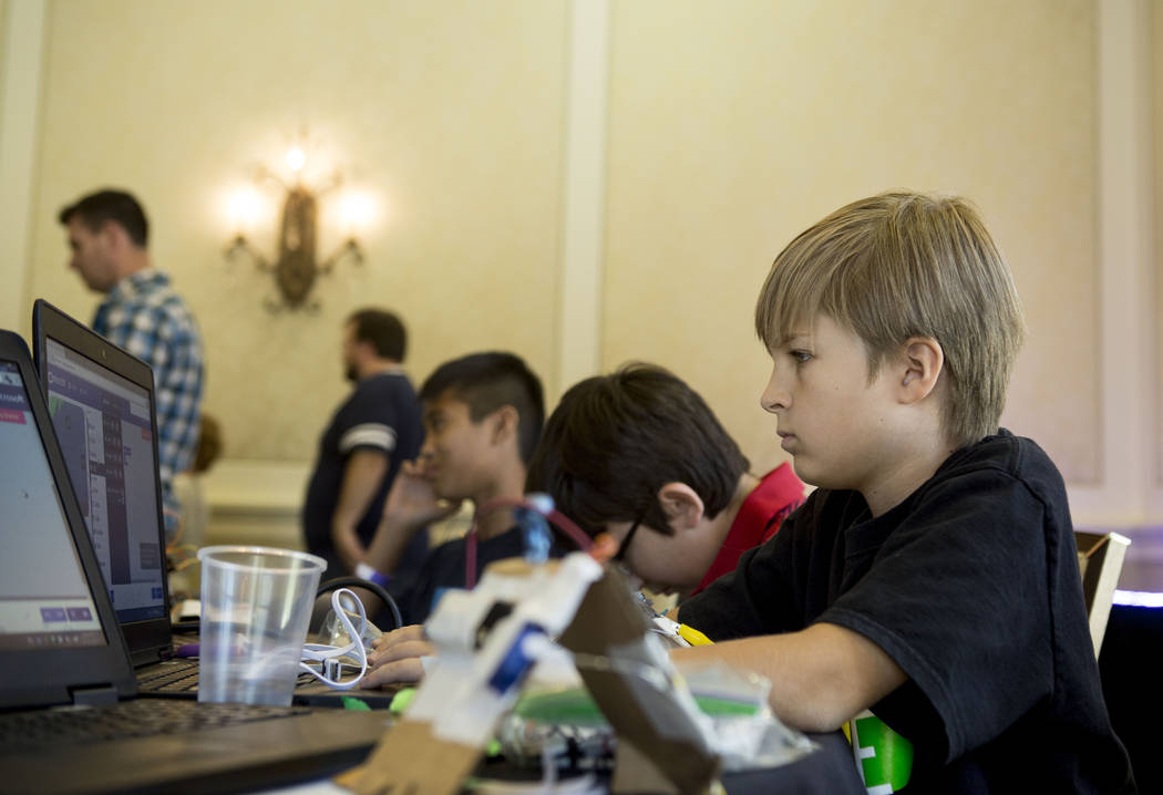 Pinecrest Academy student Tucker Purdy, 10,  works on a coding exercise during an  interactive seminar on cyber security hosted by the Colloquium for Information Systems Security Education (CISSE) ...