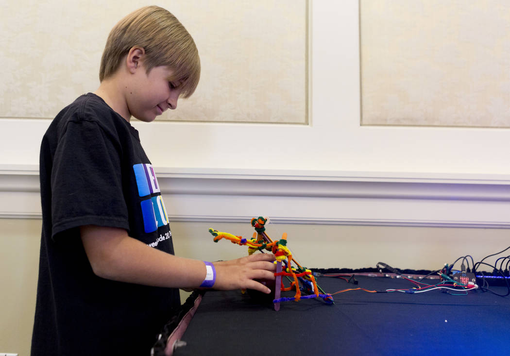 Pinecrest Academy student Tucker Purdy, 10,  looks at a robot during an interactive seminar on cyber security hosted by the Colloquium for Information Systems Security Education (CISSE), Sunday, J ...