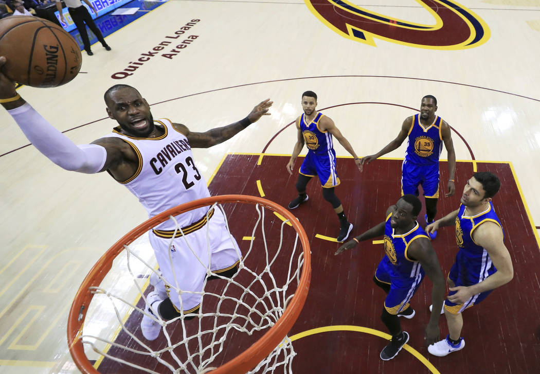 Cleveland Cavaliers forward LeBron James (23) drives to the basket against the Golden State Warriors during the first half of Game 3 of basketball's NBA Finals in Cleveland, Wednesday, June 7, 201 ...