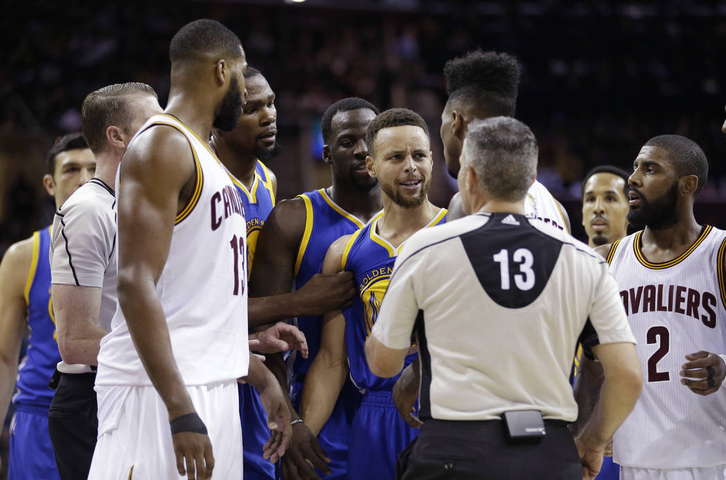 Golden State Warriors guard Stephen Curry, center,and Cleveland Cavaliers guard Iman Shumpert, on the other side of the official, argue during the first half of Game 3 of basketball's NBA Finals i ...