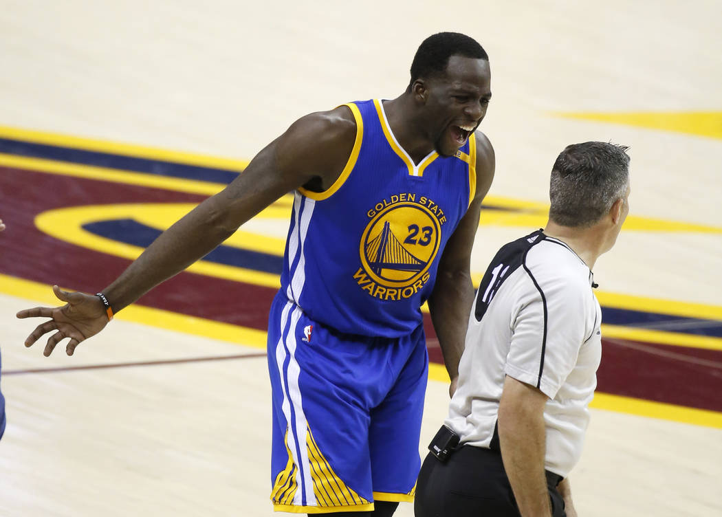 Golden State Warriors forward Draymond Green (23) argues with referee Monty McCutchen (13) during the first half against the Cleveland Cavaliers in Game 3 of basketball's NBA Finals in Cleveland,  ...