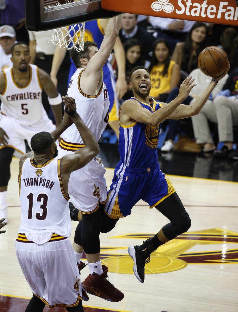 Golden State Warriors guard Stephen Curry, right, drives against the Cleveland Cavaliers during the second half of Game 3 of basketball's NBA Finals in Cleveland, Wednesday, June 7, 2017. (AP Phot ...