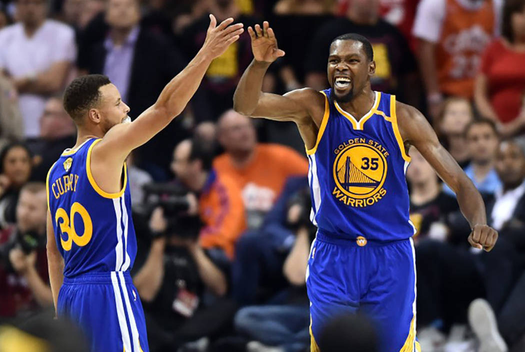 Golden State Warriors guard Stephen Curry (30) and forward Kevin Durant (35) celebrate during the fourth quarter against the Cleveland Cavaliers in game three of the 2017 NBA Finals at Quicken Loa ...