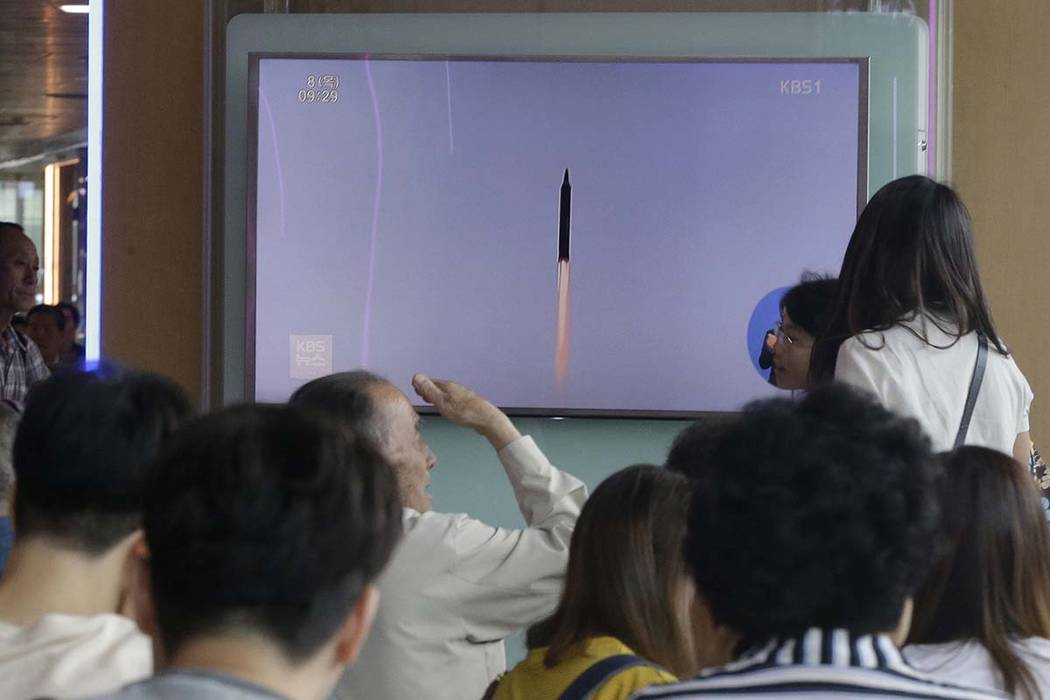 People watch a TV news program showing a file footage of a missile launched by North Korea, at Seoul Railway Station in Seoul, South Korea, Thursday, June 8, 2017. North Korea fired several projec ...