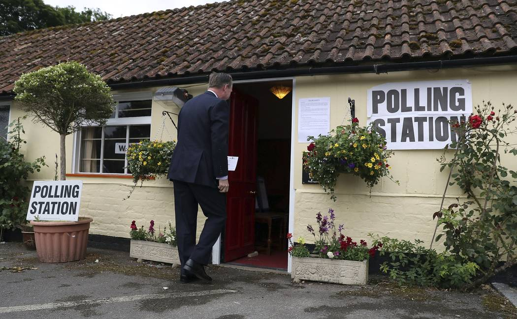 A man enters the polling station at the Golden Pheasant Public House in Lower Farringdon, Hampshire, England Thursday June 8, 2017. Polls are open from 7 a.m. to 10 p.m. (0600GMT to 2100GMT) Thurs ...