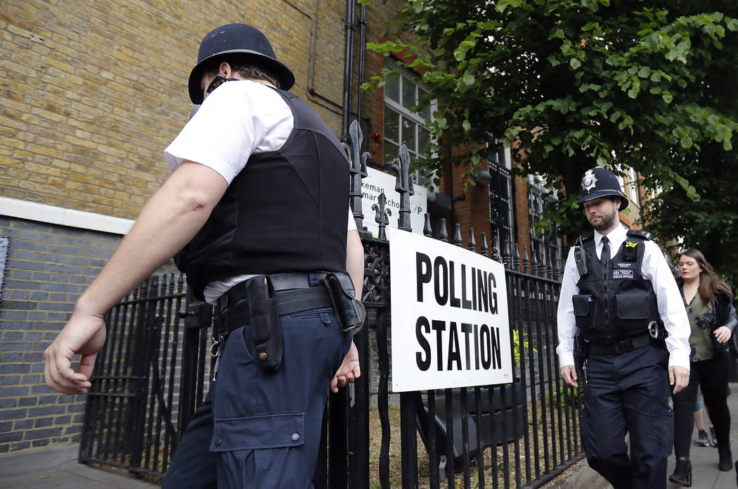 Policer officers arrive to enter a polling station in London ahead of the arrival of Britain's Labour party leader Jeremy Corbyn who will vote in the general election Thursday, June 8, 2017. (AP P ...