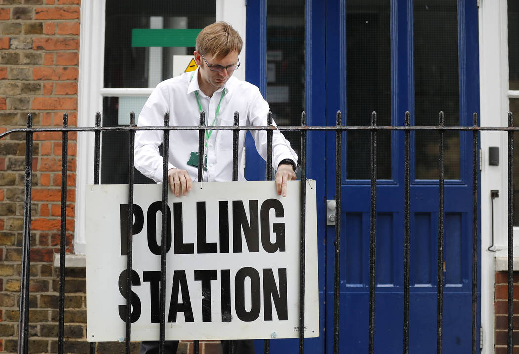 A man fixes a sign to the railings outside a polling station in London ahead of the arrival of Britain's Labour party leader Jeremy Corbyn who will vote in the general election Thursday, June 8, 2 ...