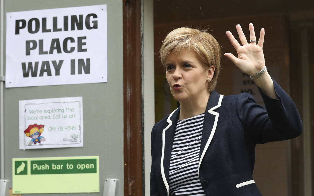 Scottish First Minister Nicola Sturgeon waves as she arrives to cast her vote in the general election at a polling station at Broomhouse Community Hall in Glasgow Thursday, June 8, 2017. Polling s ...