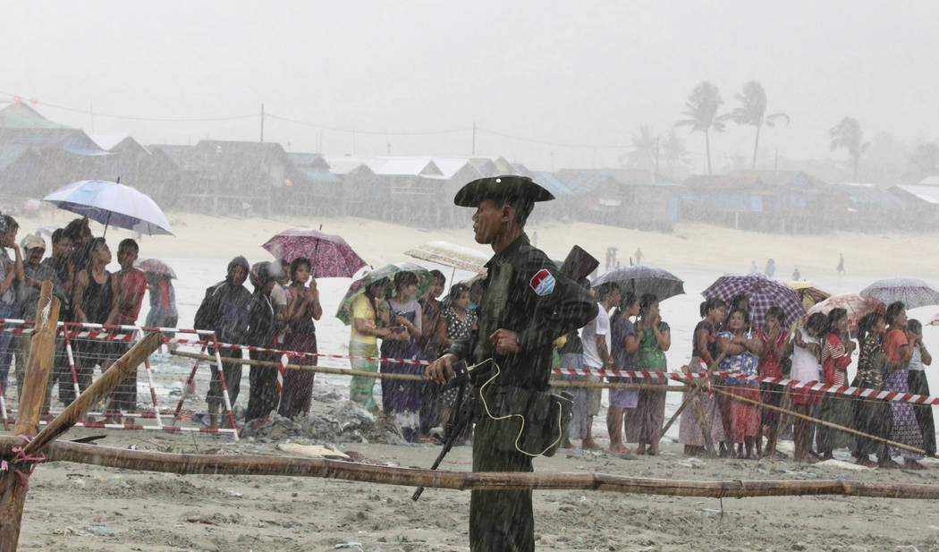 A soldier stands guard in the heavy monsoon rains as onlookers watch bodies being recovered in the waters off San Hlan village, in Laung Lone township, southern Myanmar, Thursday, June 8, 2017. Fi ...