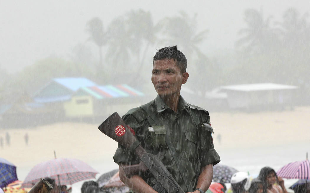 A soldier weathers monsoon rain as bodies are recovered of the waters off San Hlan village, in Laung Lone township, southern Myanmar, Thursday, June 8, 2017. Fishermen have joined navy and air for ...