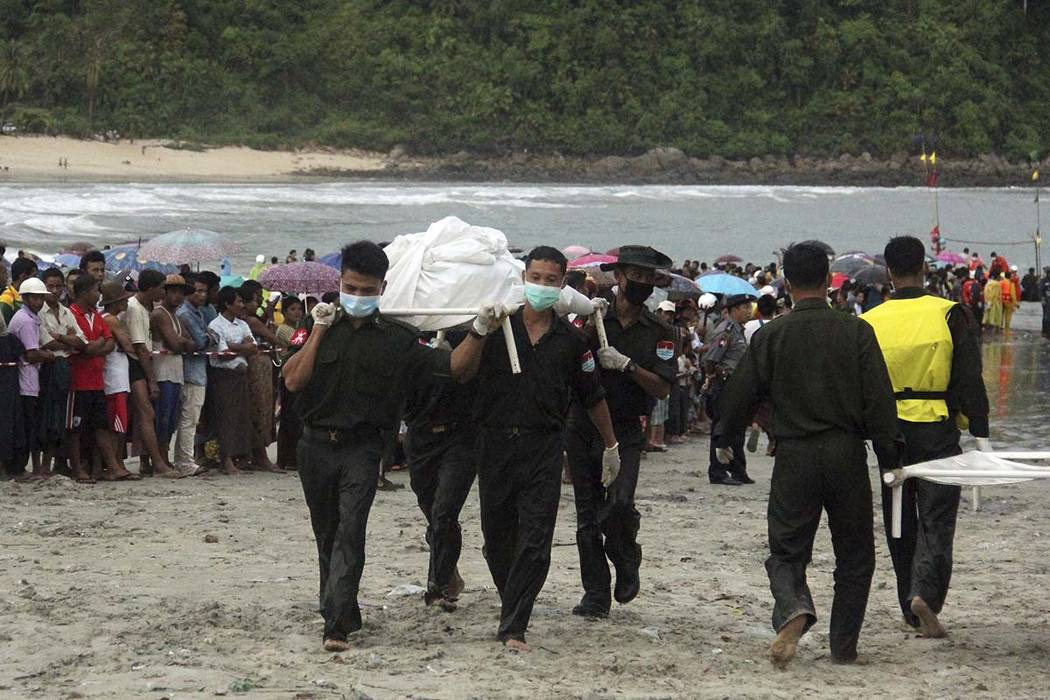 Hundreds of locals look on as rescue personnel carry bodies recovered by fishing vessels in the waters off San Hlan village, in Laung Lone township, southern Myanmar, Thursday, June 8, 2017. Fishe ...