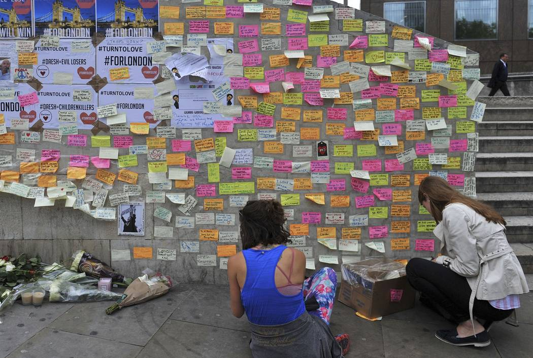 People leave messages of support on the base of the obelisk on London Bridge Thursday June 8, 2017, after an unidentified man left a box of tape, sticky notes and marker pens with an invite to wri ...