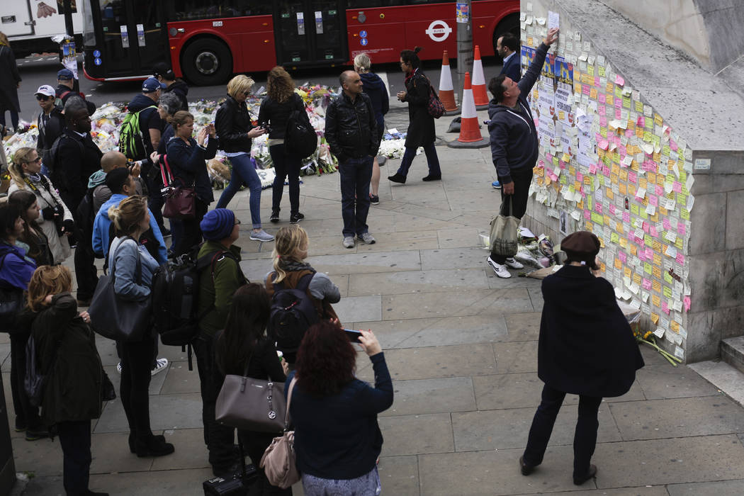A man fixes a paper between other messages against Saturday's attack on a wall near the London Bridge in London, Thursday, June 8, 2017. British voters went to the polls Thursday for an election e ...