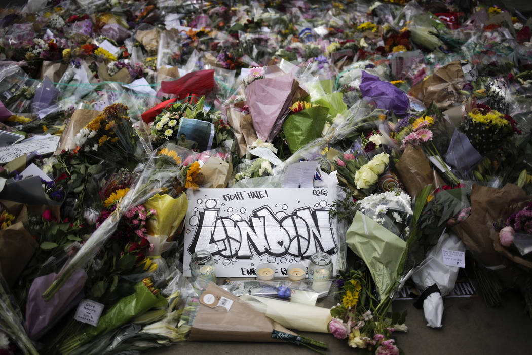 A London poster lays between floral tributes for the victims of Saturday's attack near the London Bridge in London, Thursday, June 8, 2017. British voters went to the polls Thursday for an electio ...