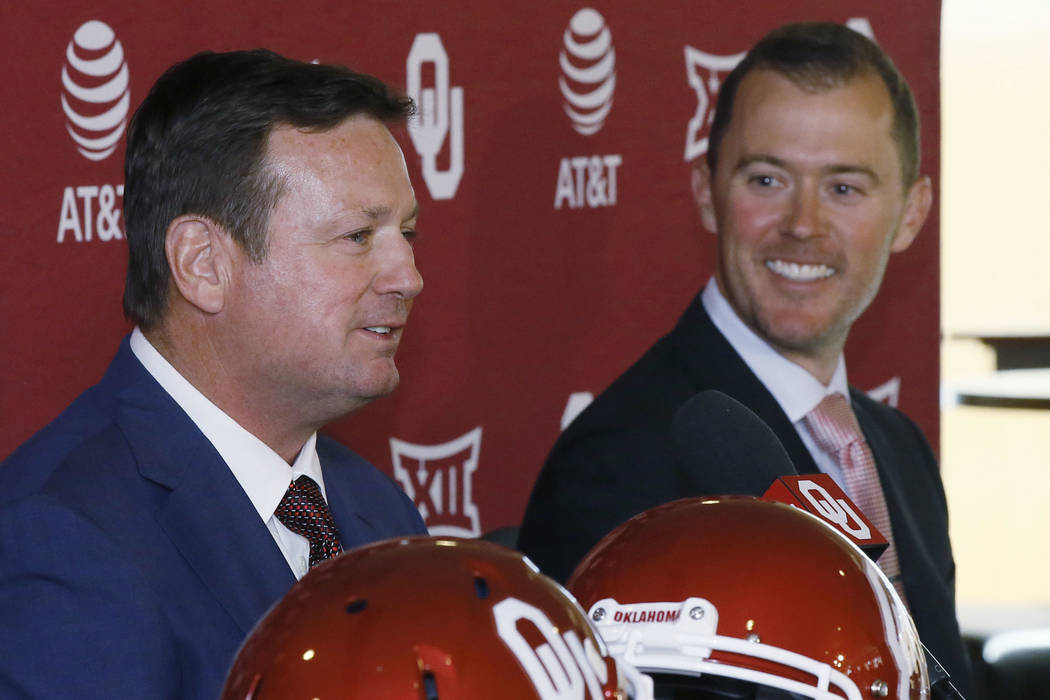 Oklahoma head football coach Bob Stoops, left, and offensive coordinator Lincoln Riley, right, laugh at a news conference to announce the retirement of Stoops in Norman, Okla., Wednesday, June 7,  ...