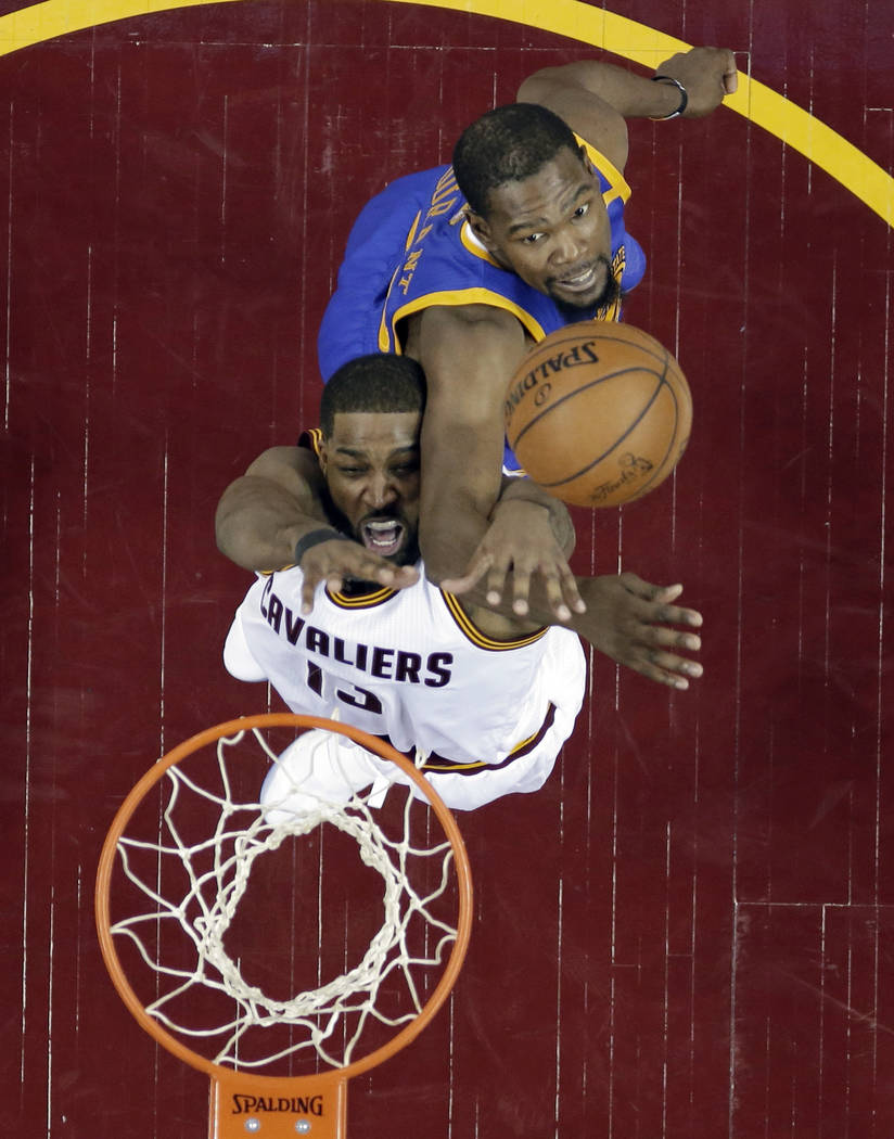 Cleveland Cavaliers' Tristan Thompson, bottom, is stopped by Golden State Warriors' Kevin Durant during the first half of Game 3 of basketball's NBA Finals, Wednesday, June 7, 2017, in Cleveland.  ...