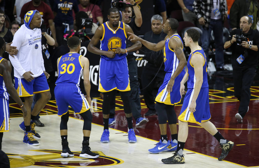 Golden State Warriors forward Kevin Durant (35) celebrates with teammates after the Warriors defeated the Cleveland Cavaliers 118-113 in Game 3 of basketball's NBA Finals in Cleveland, Wednesday,  ...