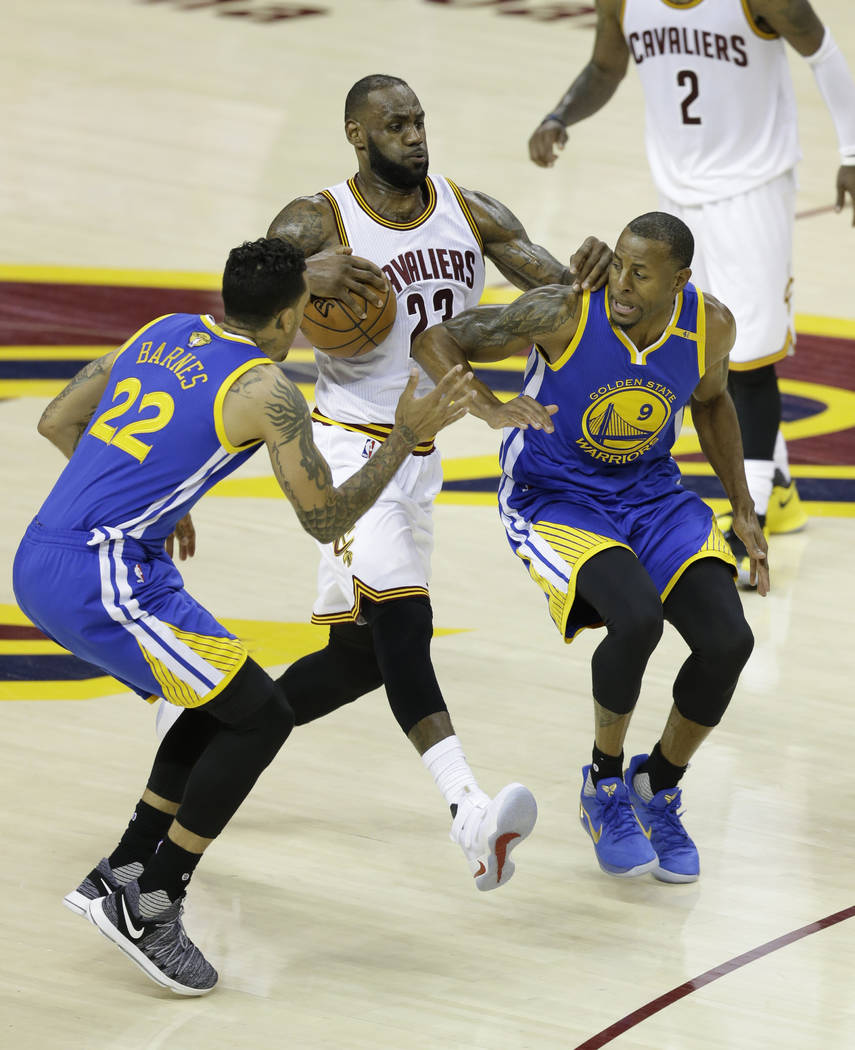 Cleveland Cavaliers forward LeBron James (23) drives between Golden State Warriors forward Matt Barnes (22) and Andre Iguodala (9) during the second half of Game 3 of basketball's NBA Finals in Cl ...