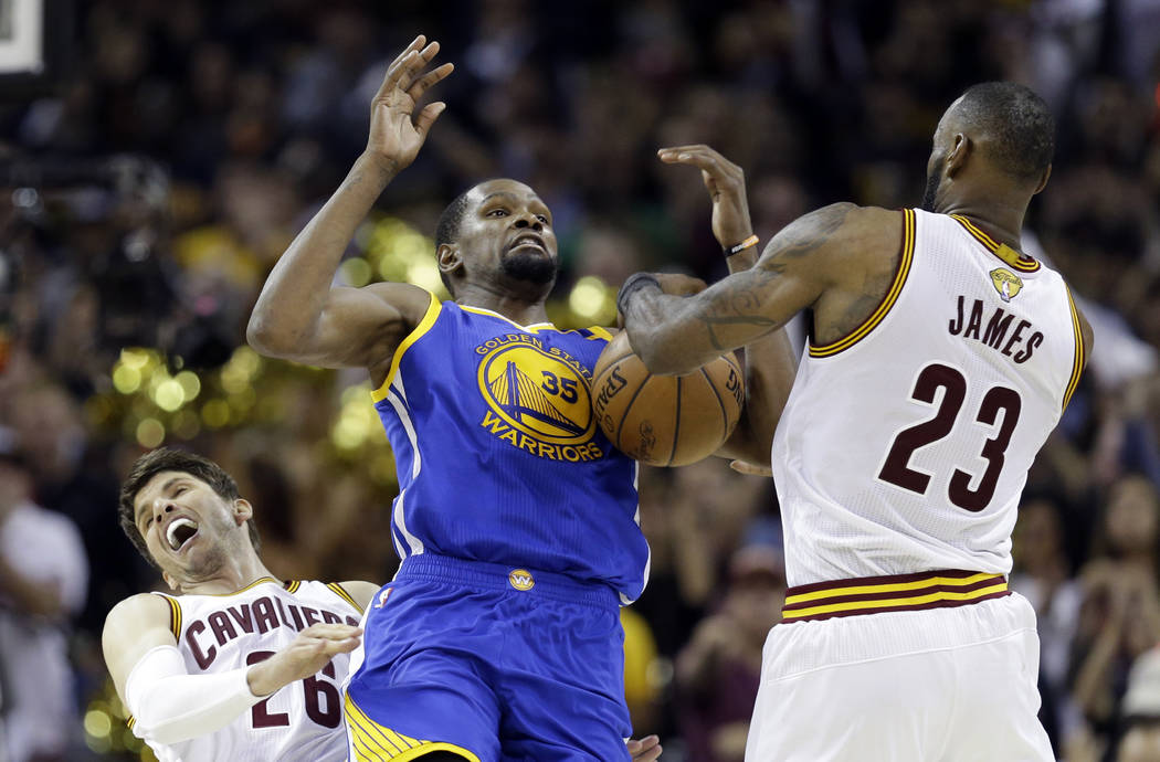 Golden State Warriors forward Kevin Durant (35) and Cleveland Cavaliers forward LeBron James (23) vie for a loose ball during the second half of Game 3 of basketball's NBA Finals in Cleveland, Wed ...