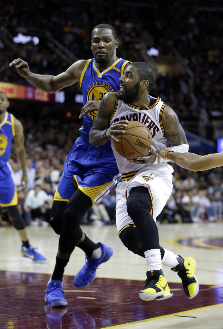 Cleveland Cavaliers guard Kyrie Irving (2) drives on Golden State Warriors forward Kevin Durant (35) during the second half of Game 3 of basketball's NBA Finals in Cleveland, Wednesday, June 7, 20 ...
