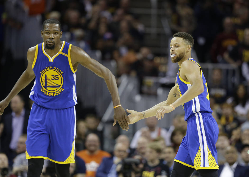 Golden State Warriors forward Kevin Durant (35) and Stephen Curry (30) play against the Cleveland Cavaliers during the second half of Game 3 of basketball's NBA Finals in Cleveland, Wednesday, Jun ...