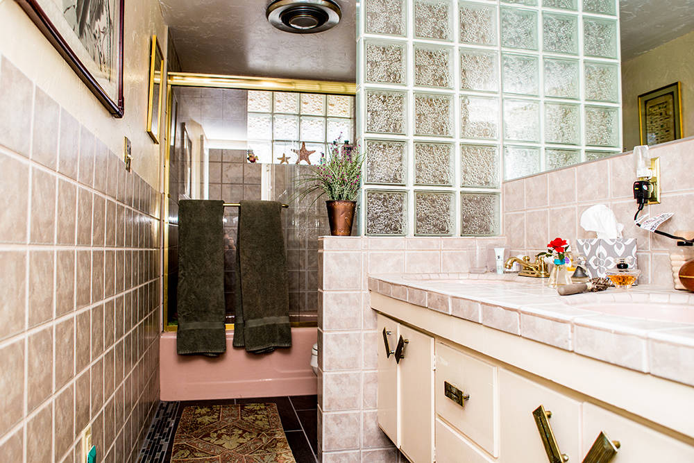 Other rooms were left untouched to preserve the original charm. One bath has a pink tub and matching pink sinks with a glass block wall accent, which in 1964 was a new trend. (Tonya Harvey Real Es ...