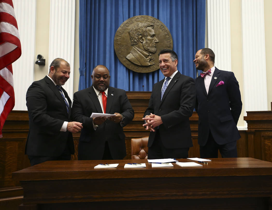 Assembly Minority Floor Leader Paul Anderson, R-Las Vegas, left, and Assembly Speaker Jason Frierson, D-Las Vegas, look at the $25,000,000 check from an anonymous donor for the UNLV medical school ...