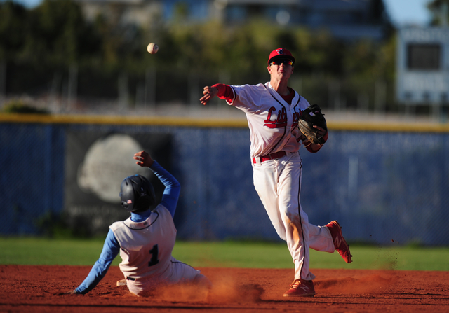 Liberty shortstop Jacob Rogers turns a double play while Centennial base runner Cole Moreno slides into second base in the second inning of their prep baseball game at Centennial High School in La ...
