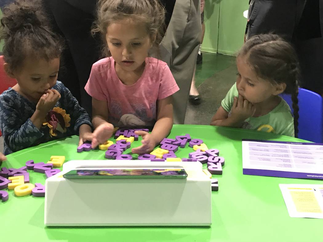 Alexandria, 3, and 5-year-old twins Isabelle and Crystal demonstrate Square Panda's multi-sensory phonics learning system for early literacy skills June 6 at Shade Tree, 1 W. Owens Ave.