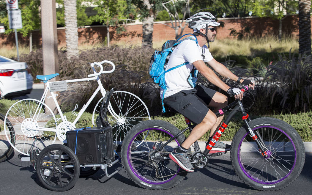 Pat Treichel, founder Ghost Bikes Las Vegas, tows the ghost bike of Dr. Kayvan Khiabani during a group ride along South Pavillion Center Drive near West Charleston Boulevard on Saturday, June 17,  ...