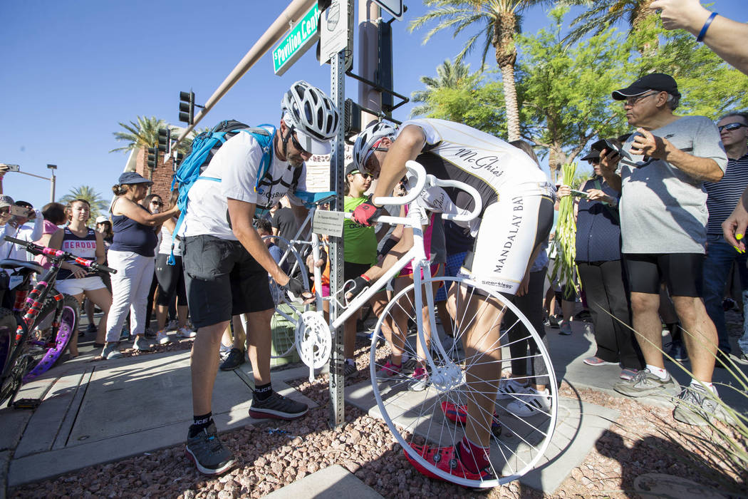 Ghost Bikes Las Vegas founder Pat Treichel, left, and fellow cyclist Michael Verni set up the ghost bike of Dr. Kayvan Khiabani during a memorial service at the corner South Pavillion Center Drive ...