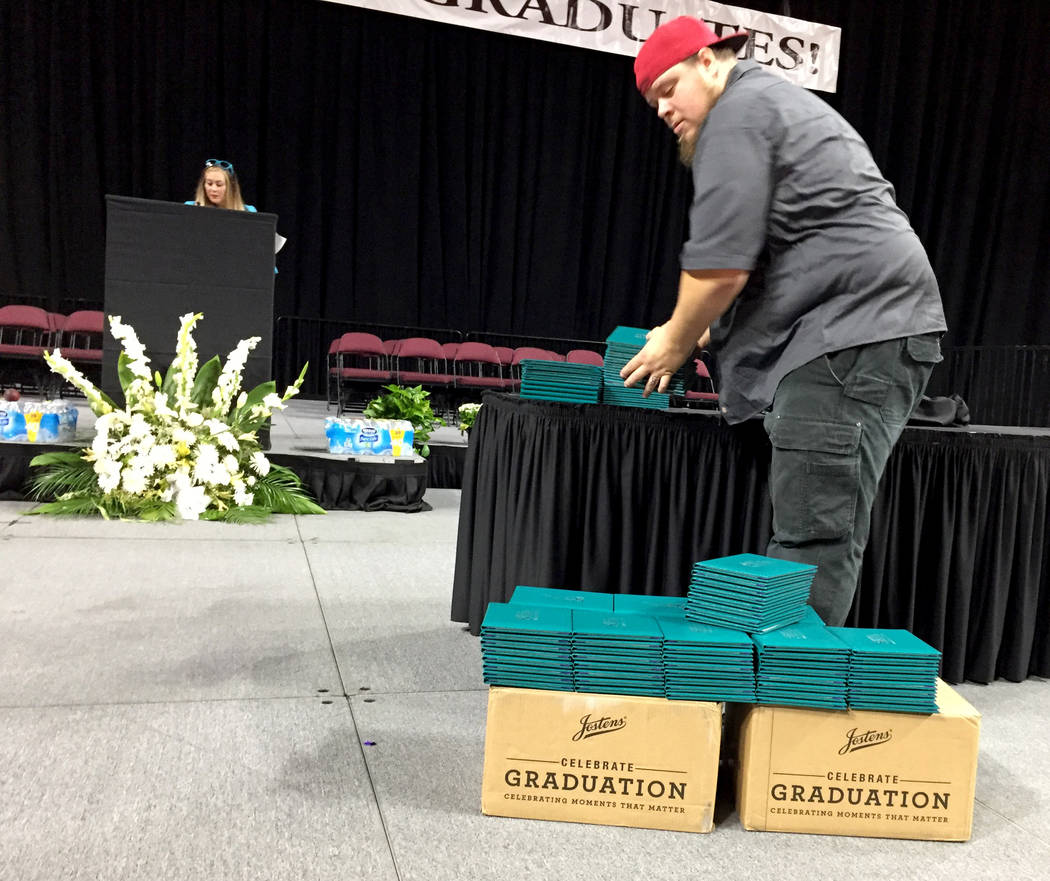 Greg Novak, a Silverado High School employee, stacks empty diplomas cases on stage at Orleans Arena Wednesday morning. A combination of district and arena employees work together to make graduatio ...