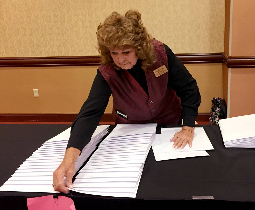 Phylis Lackie, an usher at Orleans Arena, arranges Silverado High School diplomas at the arena Wednesday morning. During the ceremony, Lackie was in charge of keeping the room secure. Meghin Delan ...