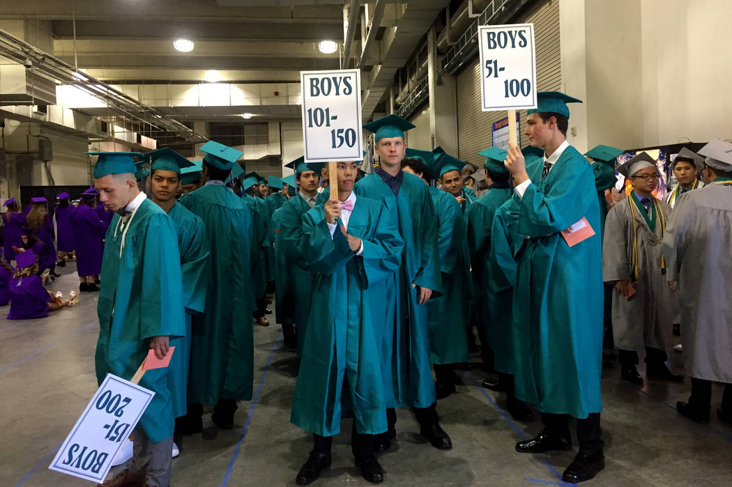 Silverado High School students wave numbered signs to help graduates get in line before proceeding into the ceremony at Orleans Arena on Wednesday morning. The arena will host 28 graduations this  ...