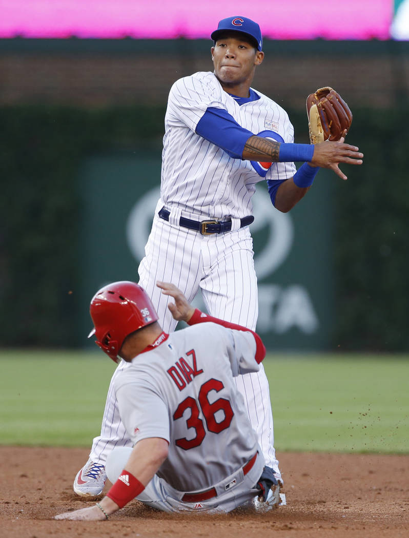 This June 4, 2017, file photo shows Chicago Cubs shortstop Addison Russell, top, throwig out St. Louis Cardinals' Michael Wacha at first base after forcing out Aledmys Diaz at second during the th ...