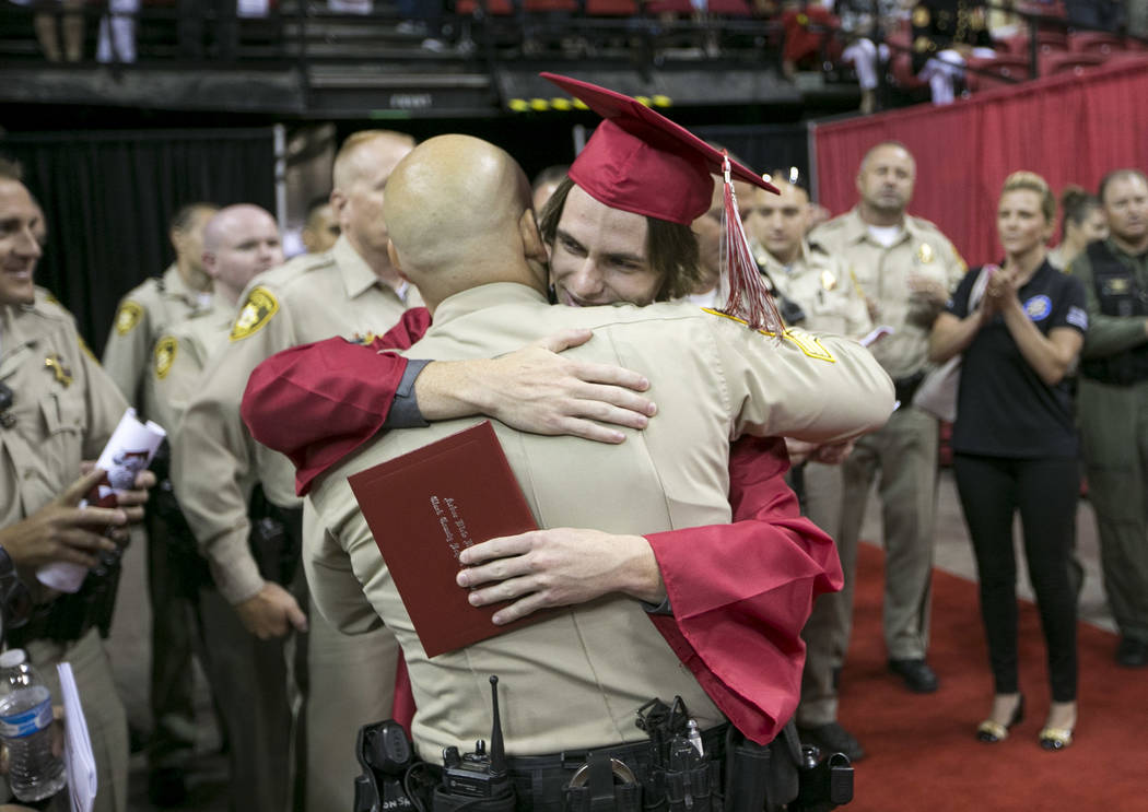 Daxton Beck hugs Metro Sergeant Eric Hutchason following his graduation ceremony at Thomas and Mack in Las Vegas on Saturday, June 10, 2017. Richard Brian Las Vegas Review-Journal @vegasphotograph