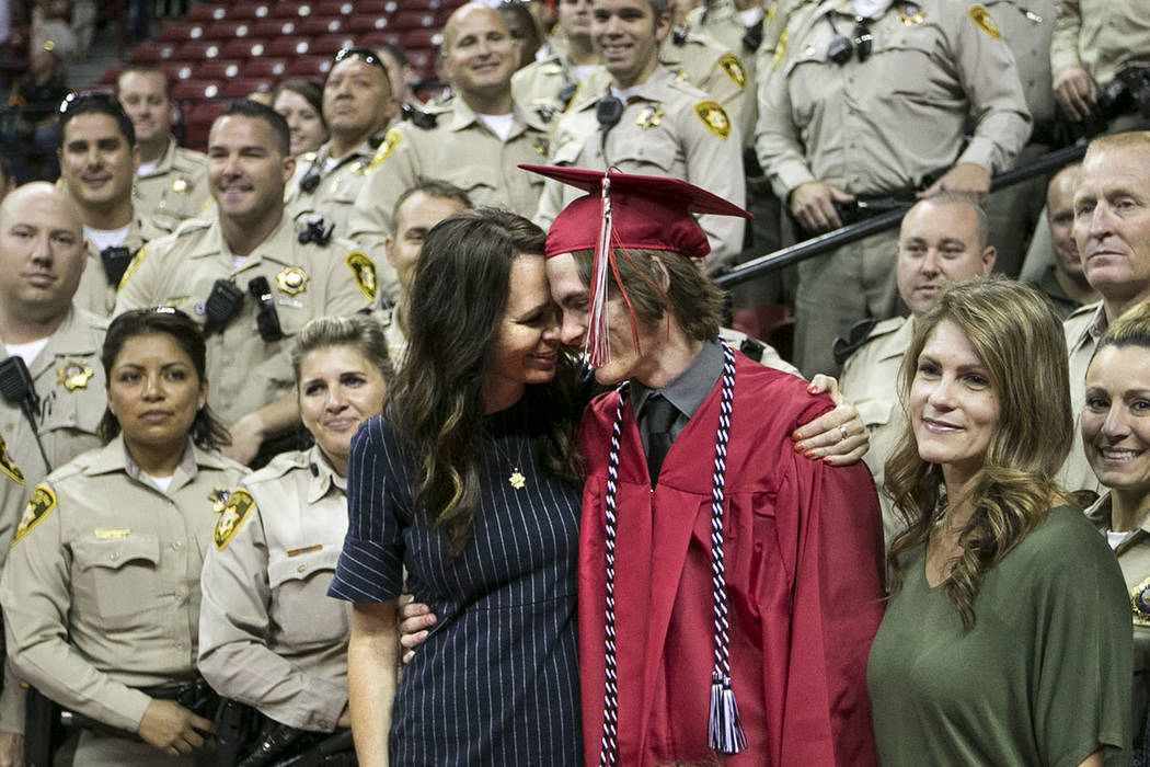 Daxton Beck gets a hug from his mother Nicole Beck as they gather for a photo with a group of Metro Officers following his graduation ceremony at Thomas and Mack in Las Vegas on Saturday, June 10, ...