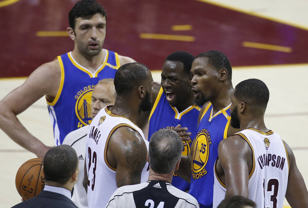 Cleveland Cavaliers forward LeBron James (23) argues with Golden State Warriors' Draymond Green (23) and Kevin Durant (35) during the second half of Game 4 of basketball's NBA Finals in Cleveland, ...