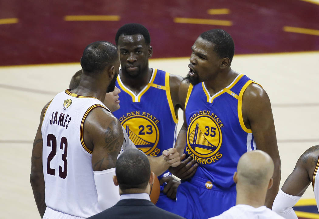 Golden State Warriors forward Kevin Durant (35) argues with Cleveland Cavaliers forward LeBron James (23) during the second half of Game 4 of basketball's NBA Finals in Cleveland, Friday, June 9,  ...