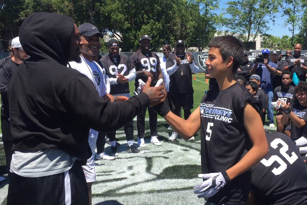 Raiders running back Marshawn Lynch (left) congratulates a teen who was presented the Best Sportsmanship Award at a football camp the Raiders hosted at their facility in Alameda, Calif., on June 1 ...