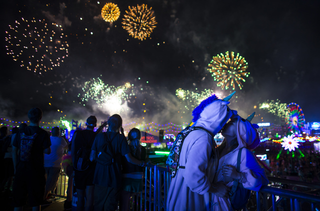 Donald Meissner, left, and Laura Wu, both of Long Beach, Calif., kiss as fireworks go off during the first night of Electric Daisy Carnival at the Las Vegas Motor Speedway in Las Vegas during the  ...