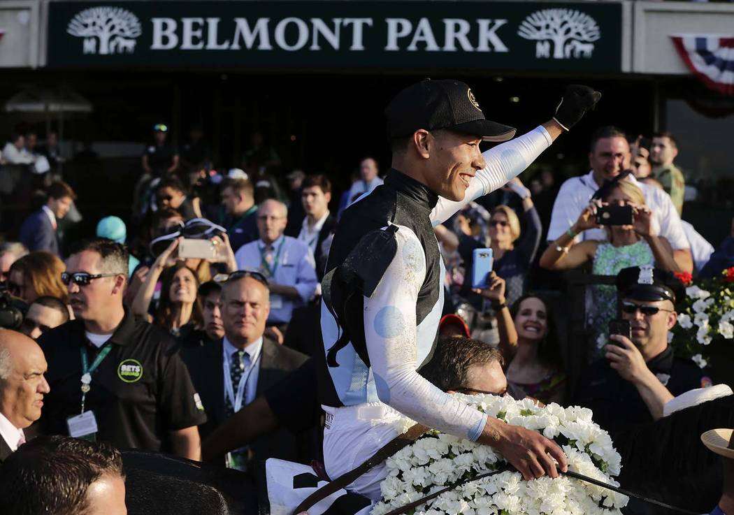Jose Ortiz raises his hand as he rides Tapwrit to the winners circle after winning the 149th running of the Belmont Stakes horse race, Saturday, June 10, 2017, in Elmont, N.Y. (AP Photo/Peter Morgan)