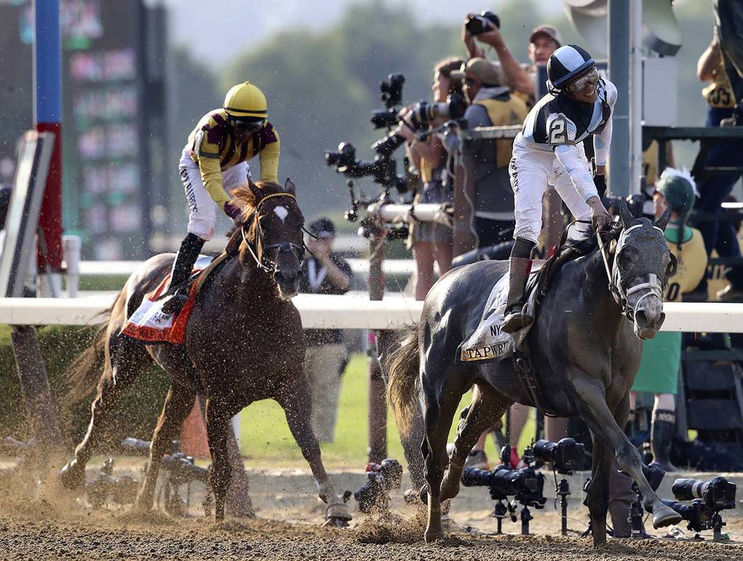 Jose Ortiz celebrates after riding Tapwrit to victory in the 149th running of the Belmont Stakes horse race, Saturday, June 10, 2017, in Elmont, N.Y. Irish War Cry, ridden by Rajiv Maragh, is at l ...
