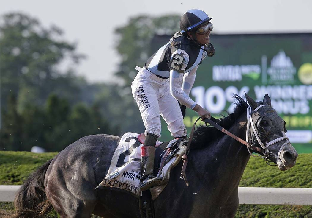 Jose Ortiz rises from his saddle after riding Tapwrit to victory in the 149th running of the Belmont Stakes horse race, Saturday, June 10, 2017, in Elmont, N.Y. (AP Photo/Peter Morgan)