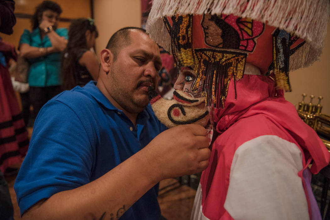 "Luis Garcia fixes the mask on his daughter, Mia Garcia, 4, before the ""chinelos"" dance took place at the ""I Am An Immigrant"" celebration event at the Asian Cult ..."