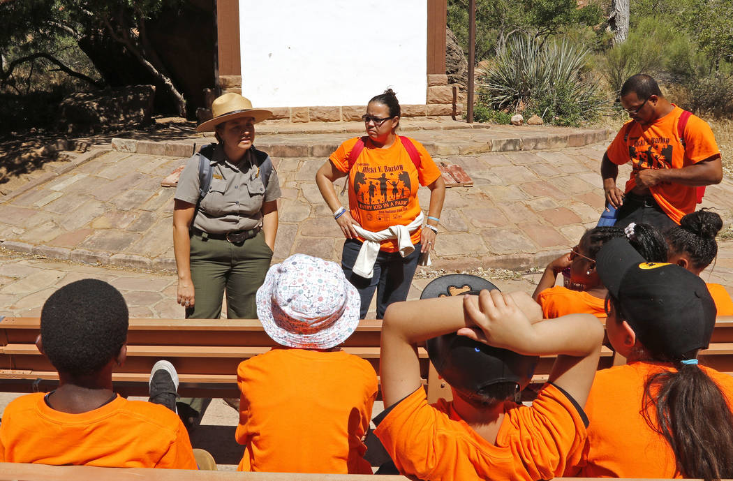 Fourth graders from Wendell P. Williams Elementary School and Victory Mission Baptist Church listen to Park Ranger Andi Buttram explain the trails they'll be hiking, Saturday, June 10, 2017. One h ...